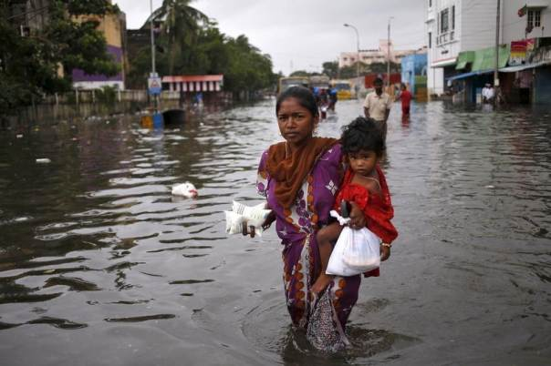 A woman carries her child and milk packets as she wades through a flooded street in Chennai, India, Dec. 5, 2015. REUTERS/Anindito Mukherjee