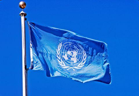 un-flag-flying-pole-blue-sky-behind-it